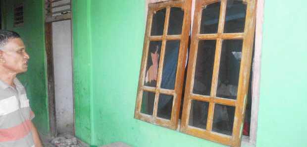 Seorang warga Mangga Dua, Reo sedang menatap kaca jendela rumahnya yang pecah akibat dilempari batu oleh warga Mata Air (Foto: Floresa/Ardy Abba)