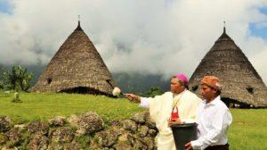 Uskup Hubert Leteng, Pr sedang menyiram halaman rumah adat Wae Rebo dengan air berkat.